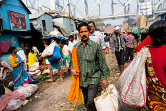Man with the a bunch of flowers rushing through the market in Calcutta Royalty Free Stock Photos