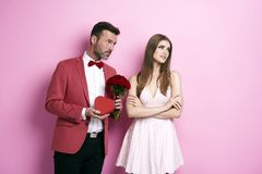 Perfect way to apologise. Man with bunch of rose and chocolate box apologizing fiancée Stock Photo