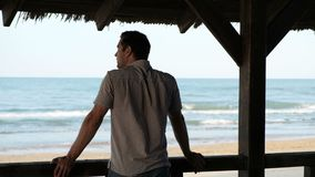 A man from a bungalow looks at the sea stock footage