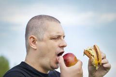 Man with burger and apple Royalty Free Stock Photography