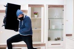 The man burglar stealing tv set from house. Man burglar stealing tv set from house stock image