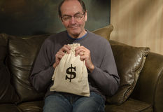 Man with burlap bag and dollar sign. Man smiling holding burlap bag with dollar sign Royalty Free Stock Photography