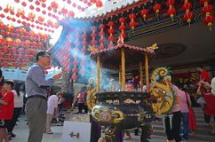 Man burn incense sticks and pray for good fortune. Kuala Lumpur, Malaysia - February 16, 2018: Man praying during Chinese New Year celebration in Thean Hou Royalty Free Stock Photo