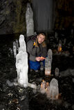 Man with a burning candle sits in a cave with ice blocks Royalty Free Stock Images