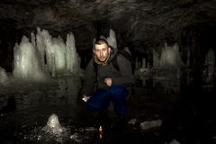 Man with a burning candle sits in a cave with ice blocks Royalty Free Stock Image