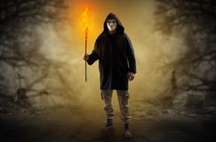 Man coming out from a thicket with burning flambeau. Man with burning flambeau coming from thicket and looking something Stock Photos