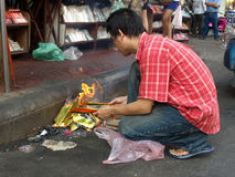 Man Burning Ghost Money During Chinese New Year. BANGKOK - FEB 14: Man burns joss paper or ghost money in an ancestor worship rite on a street in Chinatown as Stock Photo