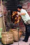 Man burning trash. Chinese temple worker burning the paper offerings and incense sticks after Dragon Boat festival in Hongkong stock photo