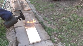 Man burns the board with a gas burner. 1 stock video footage
