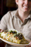 Man with burrito. Single white man in casual clothing holding up plate of Mexican burrito Stock Photography