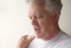 Man with bursitis. A man suffers from pain in his shoulder royalty free stock photos