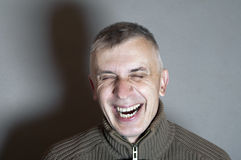 Man Bursting Into Laugh. Stdio shot of a man bursting into laugh Stock Image
