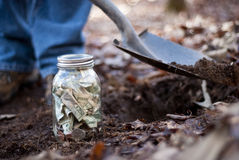 Man Burying Jar of Money Stock Images