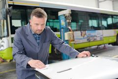 Man in bus garage cleaning panel stock photo