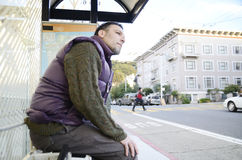Man at the bus stop. A man dressed in warm clothes waiting at a bus stop Stock Photography