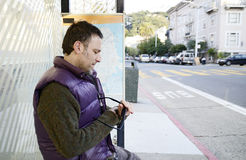 Man at a bus stop Stock Photo