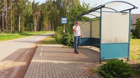 Man at bus stop. In summer day stock footage