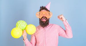 Man with bushy beard organizing fun activity for kids. Hipster with crazy look celebrating, happiness concept. Bearded. Man wearing birthday cap, huge fancy stock image