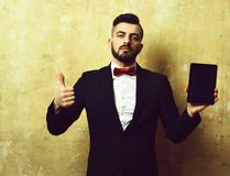 Man of business with beard holds tablet and thumb up. Man of business with beard, confident face expression and stylish outfit holds high tech tablet and shows Royalty Free Stock Images