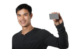 Man with Business Card. Man smiling as he holds up a small blank card off to one side Stock Image