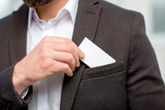 Man with business card. Elegant man in the suit putting business card into the pocket. White card to copy paste Stock Image