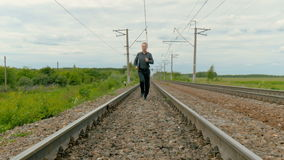 A man in business clothes is running on rails, holding a laptop in his hands. stock video
