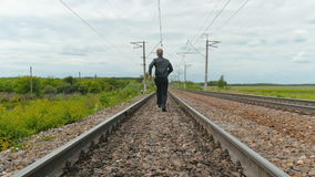 A man in business clothes is running on rails, holding a laptop in his hands. stock video footage