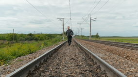 A man in business clothes is running on rails, holding a laptop in his hands. stock footage