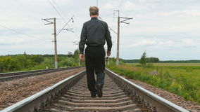 A man in business clothes is walking on rails. A man in a business suit wearing sunglasses goes by rail. Summer sunny day. Problem solved stock footage