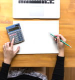 Man of business man hand working on book on wooden desk Laptop w. Ith blank screen on table Royalty Free Stock Image
