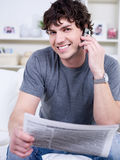 Man of business with mobile phone. Portrait of happy handsome young man with mobile phone reading newspaper - indoors Stock Photo