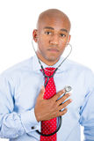 Man, business person, worker listening to his heart with stethoscope Royalty Free Stock Image
