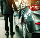 man business saleman open door car on street blurry background.For stock images