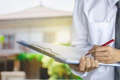 Man business salesman Sell house. With computer On house and tree blurry background.For home business contracting or agreement and home warranty image royalty free stock photo