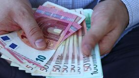 A man in a business shirt counting European money, Euro. Various banknotes