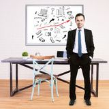 Man and business sketch. Happy businessman in suit standing in modern office with business sketch on whiteboard Royalty Free Stock Photos