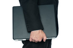 A man in a business suit carrying a notebook Royalty Free Stock Photos