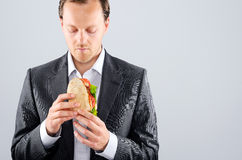 Man in business suit eating a delicious take away meat roll royalty free stock images