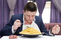 Man in a business suit eating spaghetti Stock Photo