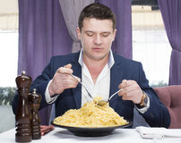 Man in a business suit eating spaghetti Stock Images