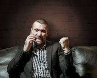 A man in a business suit an emotionally speaks on the phone Stock Photography