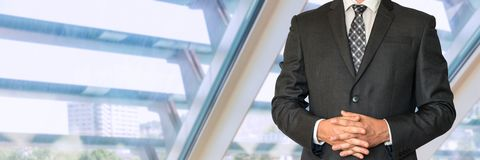 Man in business suit and folded fingers. In office Stock Photo