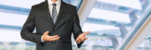 Man in business suit gestures with hands and says something. In office Stock Image