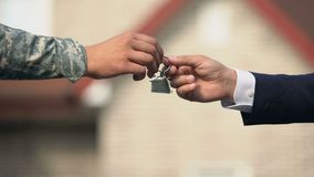 Man in business suit giving house key to man in military uniform, state support. Stock footage stock footage
