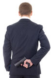 Man in business suit hiding gun behind his back isolated on whit Royalty Free Stock Photo