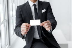 Man in a business suit holding a business card mockup Stock Photo