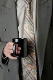 Man in business suit holding a cup of coffee Stock Image