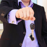 A man in a business suit holding key with remote control Stock Images