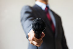 Man in business suit holding a microphone conducting a business Royalty Free Stock Image