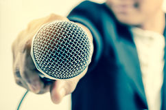 Man in business suit holding a microphone conducting a business. Interview with lighting stock photo